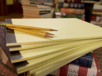 A stack of notepads with pencils